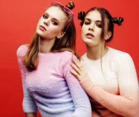 Two fashion hairstyle girls taking pictures in the studio Stock Photo 04