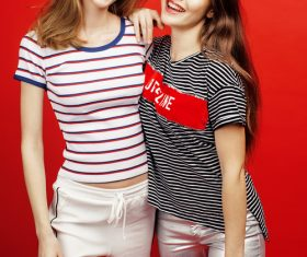 Two girls posing with red background Stock Photo 04