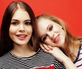 Two girls posing with red background Stock Photo 07