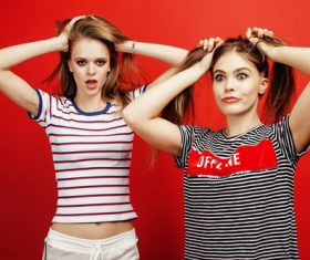 Two girls with fiddling hair take pictures in the studio Stock Photo 01