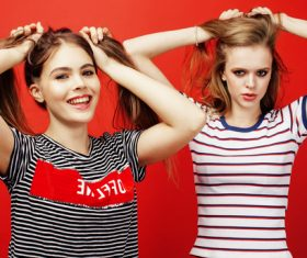 Two girls with fiddling hair take pictures in the studio Stock Photo 02