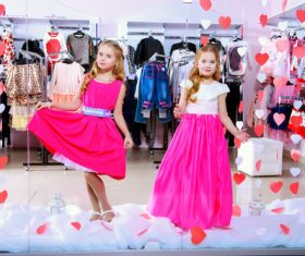 Two little girls try on clothes in front of the mall mirror Stock Photo