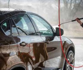 Use high pressure water gun to clean the car Stock Photo