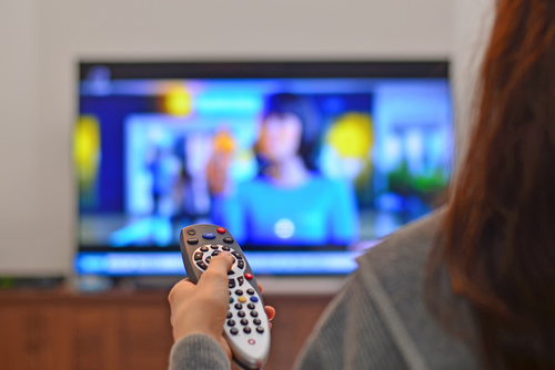 Woman holding TV remote control console Stock Photo