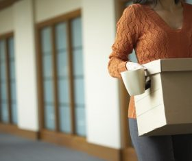 Woman holding carton box and mug Stock Photo