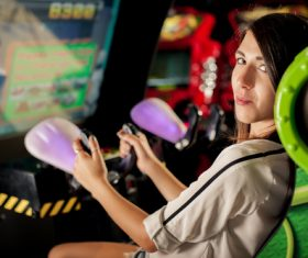 Woman playing shooting game in playroom Stock Photo