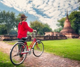 Woman pushing bicycle looking at ancient architecture Stock Photo