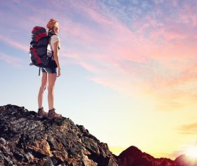 Woman standing on the mountain top watching the sunrise Stock Photo