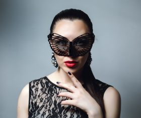 Woman wearing black butterfly mask Stock Photo 02