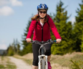 Woman wearing hardhat riding bicycle Stock Photo