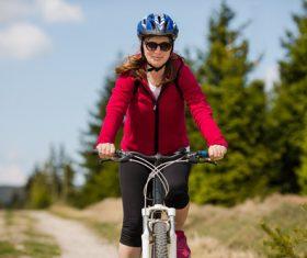 Woman wearing hardhat riding bicycle Stock Photo