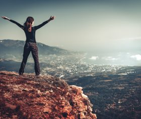 Woman with arms outstretched on the top of the mountain Stock Photo