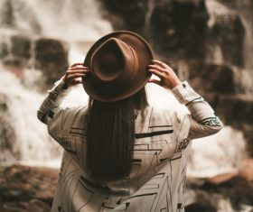 Woman with hat looking at waterfall Stock Photo