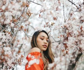 Young asian girl posing with blooming flowers Stock Photo