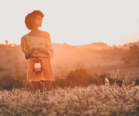 Young black woman posing on field at dusk Stock Photo