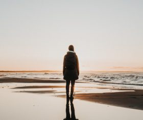 Young girl standing alone on seaside Stock Photo