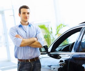 Young man standing next to new car Stock Photo
