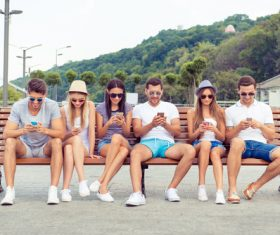 Young people sitting on bench and playing with smartphone Stock Photo