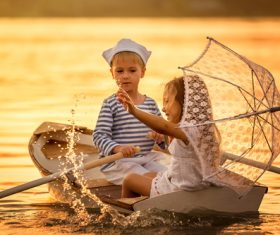 little boy boating on the lake with little girl Stock Photo 06