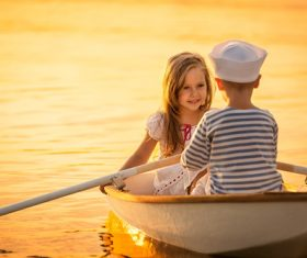 little boy boating on the lake with little girl Stock Photo 08