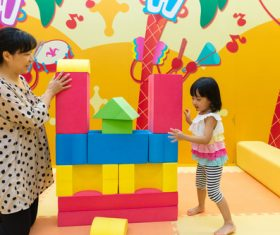 little girl and her mother together to build blocks Stock Photo