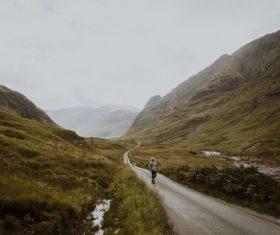 person walking mountain road Stock Photo