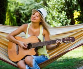 Beautiful woman sitting on hammock playing guitar Stock Photo