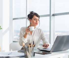 Business woman drinking coffee using laptop Stock Photo