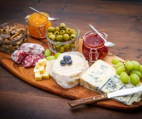 Cheese jam and sausage with pickled olives on cutting board Stock Photo 01