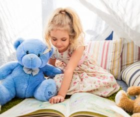 Child and teddy bear reading book together Stock Photo