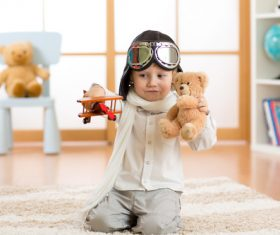 Child holding teddy bear play wooden plane Stock Photo 01