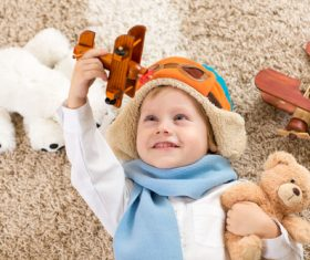 Child holding teddy bear play wooden plane Stock Photo 02