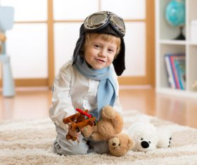 Child holding teddy bear play wooden plane Stock Photo 03