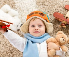 Child holding teddy bear play wooden plane Stock Photo 04