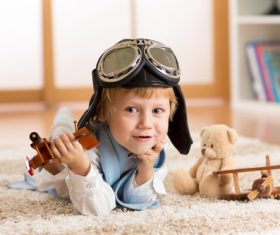 Child playing with wooden plane on the carpet Stock Photo 01