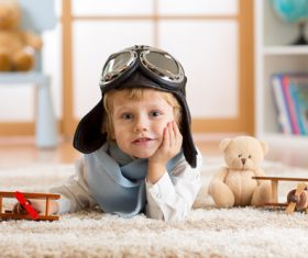 Child playing with wooden plane on the carpet Stock Photo 02