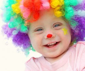 Child with colorful wig and red nose Stock Photo