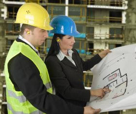 Engineer looking at drawings at construction site Stock Photo