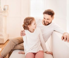 Father and daughter sitting on the couch Stock Photo