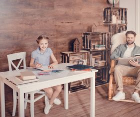 Father reading book and daughter doing homework Stock Photo
