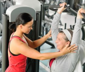 Female coach guiding the elderly to exercise Stock Photo