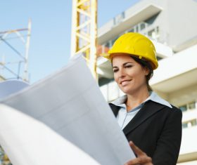 Female engineer looking at drawings at construction site Stock Photo