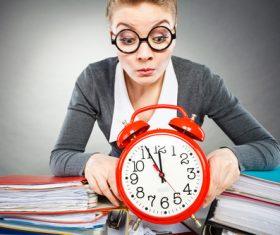Female secretary and alarm clock Stock Photo 01