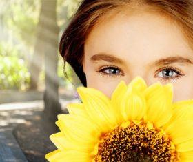 Girl holding sunflower flower covering face Stock Photo