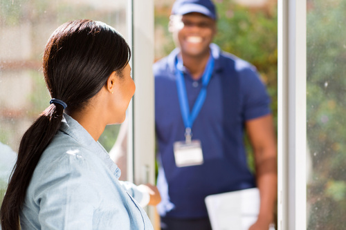 Girl opens the door waiting for express delivery Stock Photo