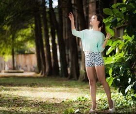 Girl posing beside the green plants Stock Photo