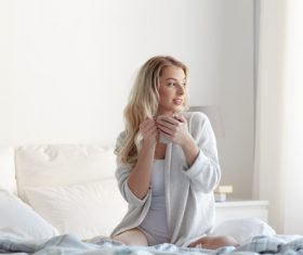 Girl sitting in bed drinking tea Stock Photo 02