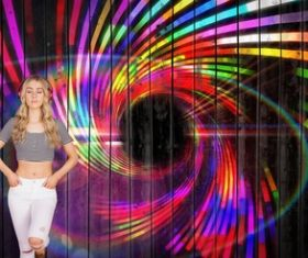 Girl standing in front of a colorful background wall wearing headphones Stock Photo