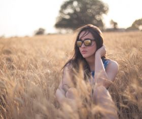 Girl with sunglasses in the wheat field Stock Photo