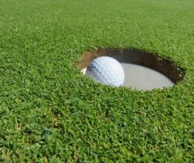Golf ball in the hole Stock Photo